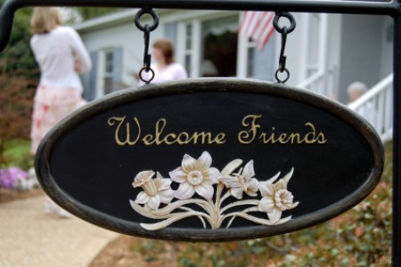 A sign in front of a house welcoming friends to visit.