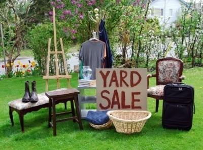 A yard sale with lots of household goods for sale.