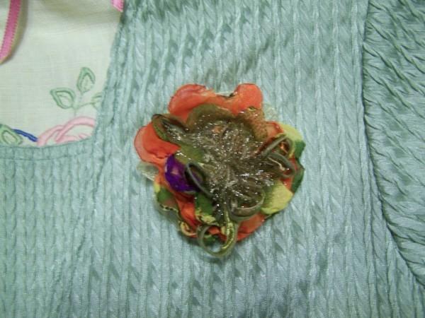 An orange and green silk flower pin.
