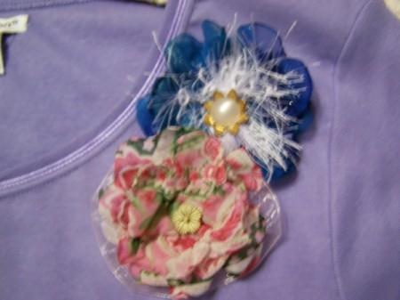 Two silk flower pins on a purple shirt.