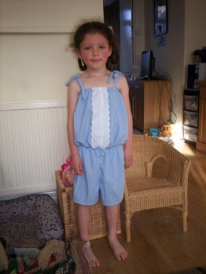 A child's jumpsuit made out of an old men's shirt.