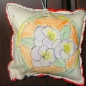 square sachet with blue pansey type flowers inside an orange circle