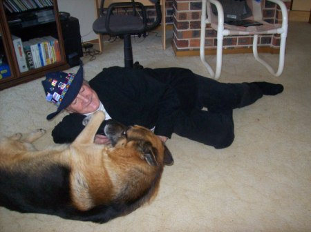 Man in a cowboy hat playing with a German Shepard