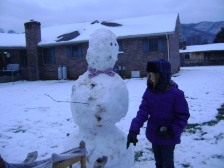 A snowman and a boy in a winter jacket.