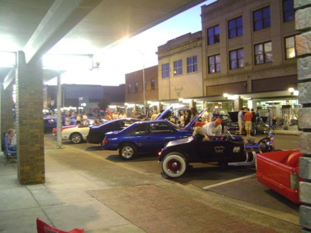 A line of classic cars on a city street.