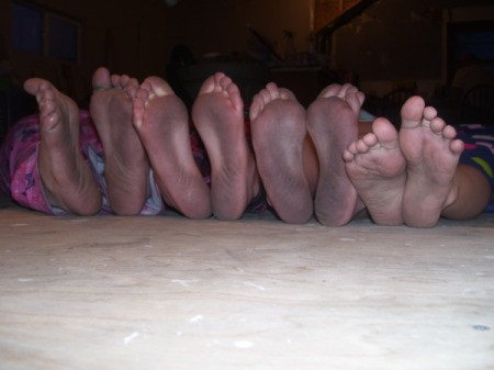 The dirty soles of four girls feet, all in a row.