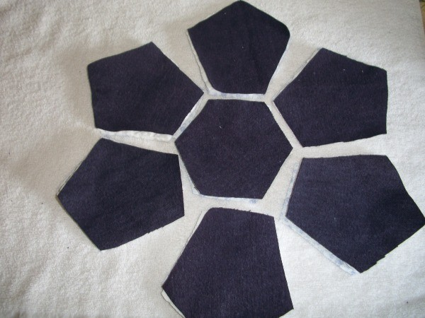 Seven fabric pieces placed in a flower shape in preparation for sewing.