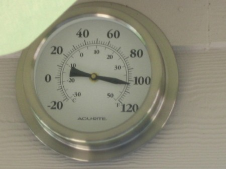 A round thermometer showing temperatures over 100 degrees F.