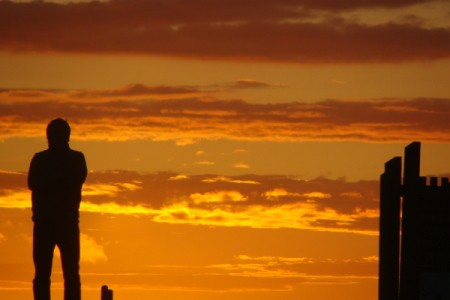 A vivid Oregon coast sunset with a silhouette of a man to the left.