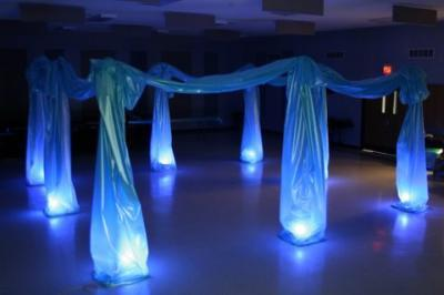 Dance floor with blue lights and draped material forming a canopy over the floor lights.