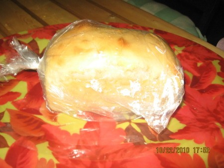 Loaf of bread wrapped in plastic wrap sitting on an orange and yellow mat