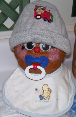 coconut with baby hat, bib, and pacifier