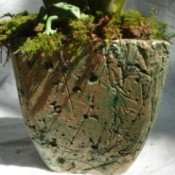 greenish brown taller planter, tapered at base
