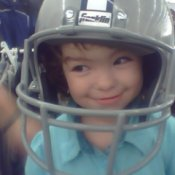 A smiling young girl with a very large Dallas Cowboys football helmet on.