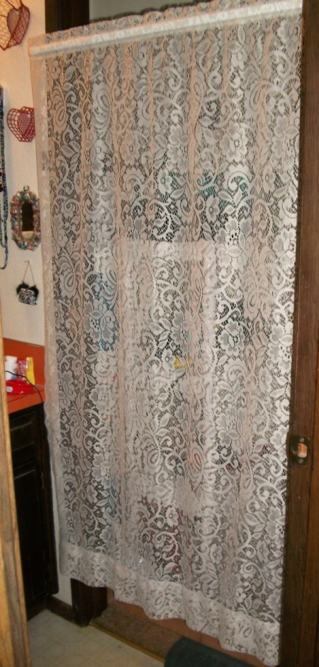 A lace curtain hiding the water heater and shelving unit.