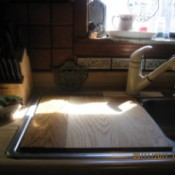 Kitchen sink with wooden cutting board cover