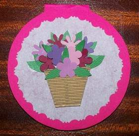 Pink circular card with basket of flowers on white doiley.