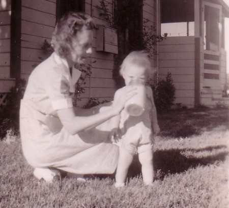 Vintage 1940's picture of mother giving toddler drink of milk