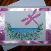 Dragonfly cut out on a card with flowers and a border