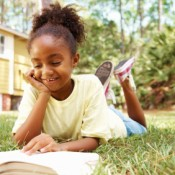 Picture of a child reading a book on the grass.