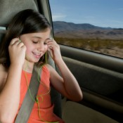 Keeping Kids Entertained on Road Trips, Photo of a child with earphones on in the back seat of a car.