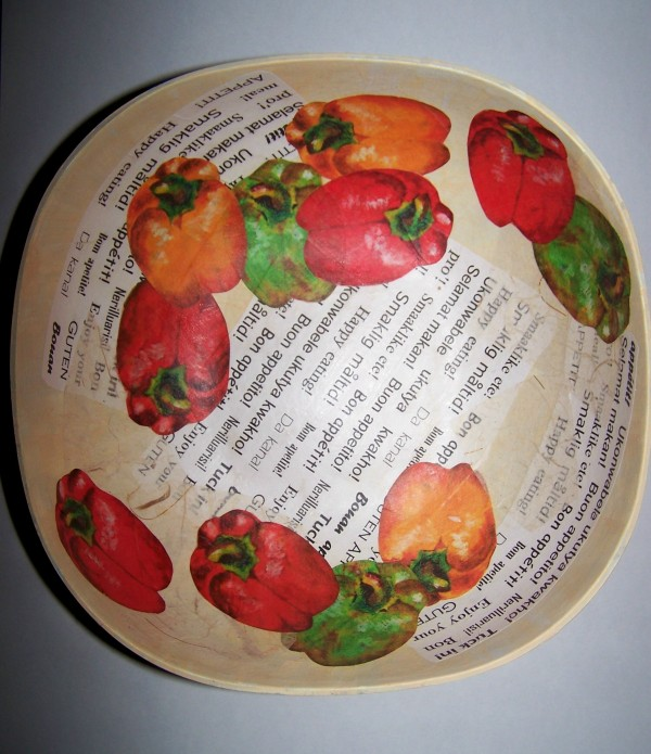 "View of interior of bowl with eleven cut outs of bell peppers arranged artfully overlapping each other and the ""word"" paper pieces."