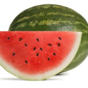A slice of watermelon in front of a full watermelon.
