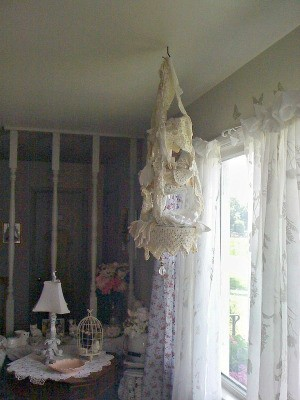 A lace chandelier in front of a window with sheer curtains.
