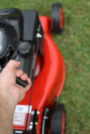 Person pulling starter cord on a red lawn mower.