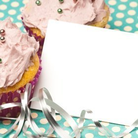 A paper invitation leaning up against two cupcakes.