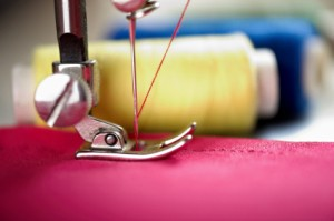 A sewing machine foot with pink thread sewing pink fabric.