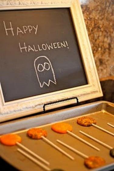 Halloween Lollipop Cookies on Cookie sheet, Happy Halloween writen ona blackboard in the backround.