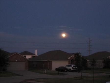 A full moon over a neighborhood.
