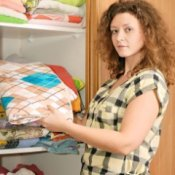 Woman holding linens in front of linen closet.