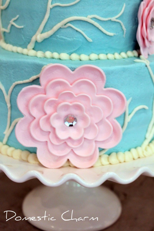 close up of a pink gumpaste flower with a rhinestone center on a teal cake siting on a cake stand
