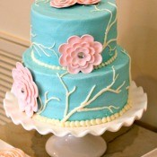 tiered teal cake with pink gumpase flowers on a cake stand
