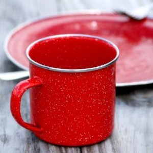Red enamel camping cup and plate on a wood table.