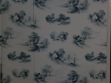 White or cream wallpaper with scattered images of country cottages, stone bridges, and a lake with a sail boat.