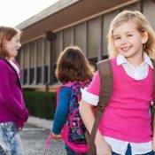 Three school age girls wearing backpacks.