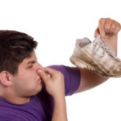 Picture of a man holding up stinky shoes.