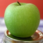 Green apple sitting on the lid of a canning jar.