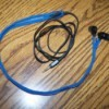blue zippered earbud cord case with earbuds inside ling on a table