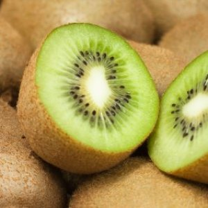 A kiwi cut in half on top of a pile of whole kiwifruit.