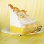 Slice of lemon meringue pie on a plate.