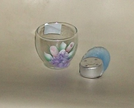 Glass Votive Holder next to a votive candle that melted into an odd shape