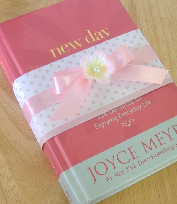 """Used Book (New Day) with pink polkadot paper """"ribbon"""" wrapped around the cover, with a pink ribbon tied in a bow and flower on top of it."""
