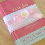 "Used Book (New Day) with pink polkadot paper ""ribbon"" wrapped around the cover, with a pink ribbon tied in a bow and flower on top of it."