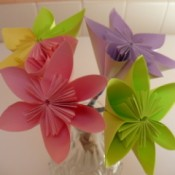bouquet of paper flowers that includes one pink flower, one purple flower, one green flower and one half yellow an half green flower.