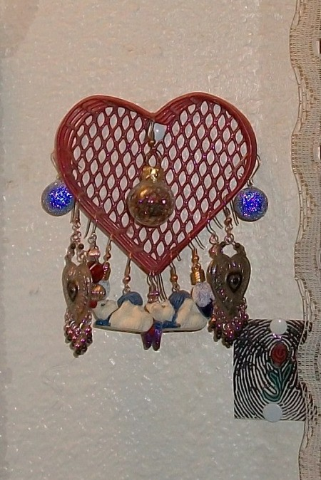 A red wire heart basket for displaying earrings.