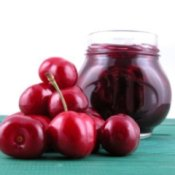 Pile of fresh cherries in front of a jar of cherry jam.